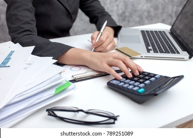 Business women using calculator at working with financial reports