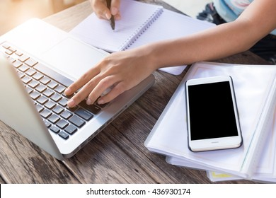 Business women using laptop and note some data on notepad