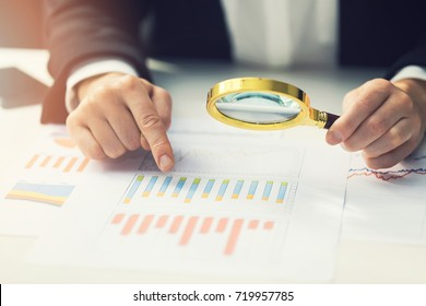 business women using magnifying glass to review financial summary chart report. auditing concept