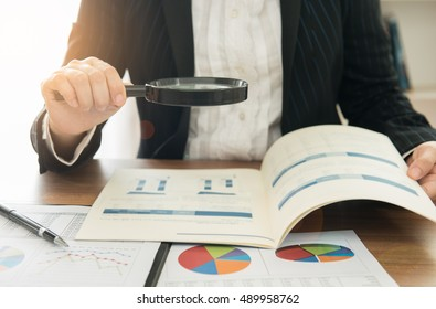 Business women using magnifying to review financial summary report. Concept of Internal audit, Auditing tax,  Analyze return on investment.