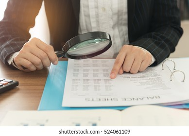 Business women using magnifying to review balance sheet annual. Concept of Internal audit, Auditing tax,  Analyze return on investment.