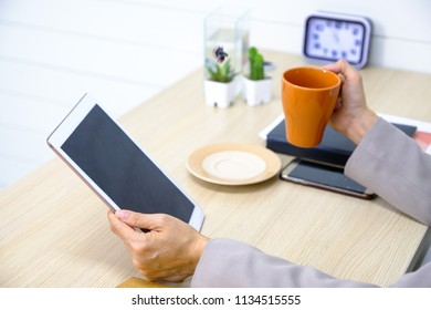 Business women who play tablet and eat coffee.