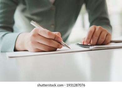 Business women write on notepad with pen to calculate financial statements within the office.