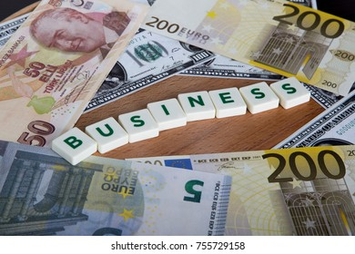 Business word with green letters among cash dollar, euro and turkish lira banknotes on wooden background.