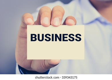 BUSINESS word on the card shown by a man, vintage tone