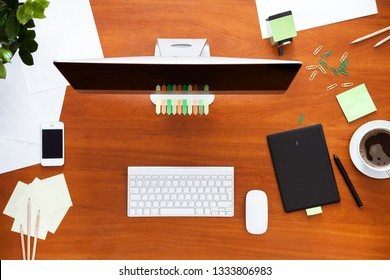 Business work desk with computer monitor keyboard mouse and supplies stationary, office table desktop designer workspace, pc on modern workplace wooden brown background, top view overhead from above