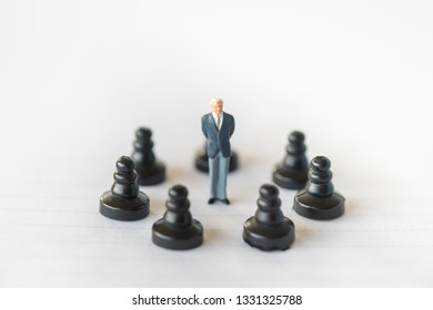 Business Work and planning concept. Close up of businessman miniature figure standing on center of round of chess pieces  on notbook