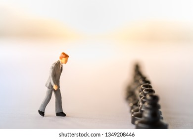 Business Work and planning concept. Close up of businessman miniature figure walking to row of black chess pieces  on notbook