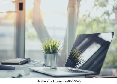 Business work table in office with laptop computer , notebook , and a cup of artificial grass for creative business work or marketing plan to success planning of company