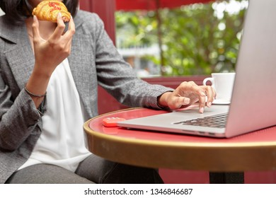 Business working in cafe while enjoying croissant