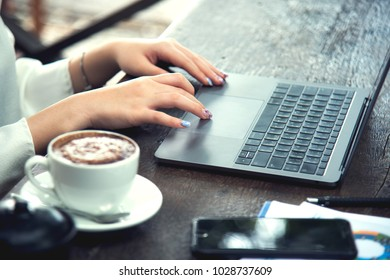 Business working concept. Businesswoman looking computer laptop.Young woman touchscreen notebook for work on website at coffee shop with wood table background.