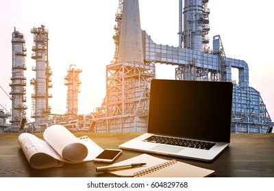 Business working Engineering Industry concept with tablet and oil refinery plant at sunset,Pipelines and petrochemical plant background