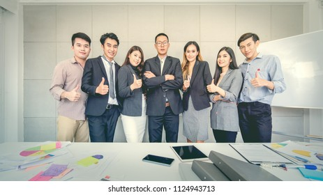 Business working goup take photography together in a row, team members having thump up while senior executive cross his arms