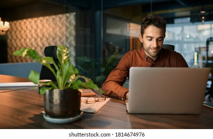 Business working on a laptop and going over paperwork while sitting at his desk in a quiet office after hours