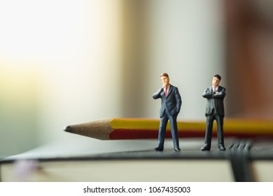 Business working and planning concept. Two businessman miniature figures standing on black notebook with pencil.
