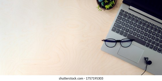 Business workspace. Online education concept. E-learning. Online training. Laptop, microphone and glasses for the computer on a wooden background, top view, copy space,banner