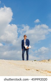 Business young man in a blue suit standing in the sand with a laptop in the hands away from the workplace