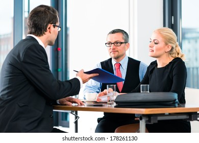 Business - young man in an Job interview, hands over his application papers to the boss and his female assistant in their office