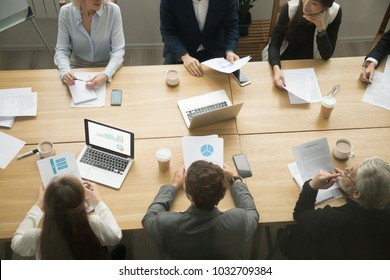 Business young and senior people group working together sitting at conference table office desk with laptops documents, corporate project team meeting or coworking teamwork concept, top closeup view