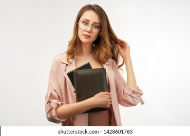 Business young woman in a stylish suit holding a notebook and a cute smile. The second her hand touches her long curly dark hair. Isolated portrait on white background.
