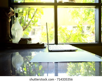 Businesses happen everywhere, just have inspiration. The picture of white laptop with Male hand on wooden table near the window at home office. selective focus