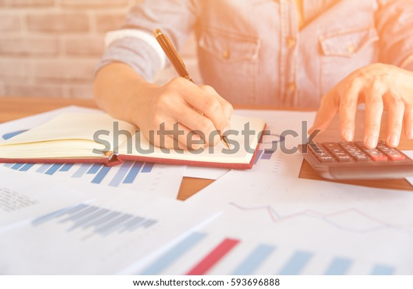 business,finance and banking concept.Close up of people hand make calculating and working with chart document on wooden table.