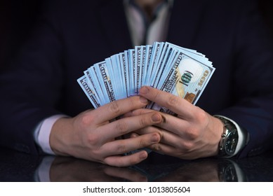 Businessman with a lot of 100 dollar bills in his hands. Rich people, successful business concept