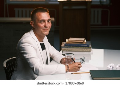 Businessman 30-35 years old in a white jacket signs important documents while sitting at the table. Closeup male portrait. Business and deal concept.