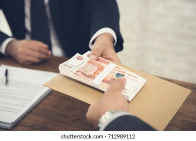 Businessman accepting Russian Ruble money with documents in an envelope from his partner after making an agreement - payment, bribery and corruption concepts
