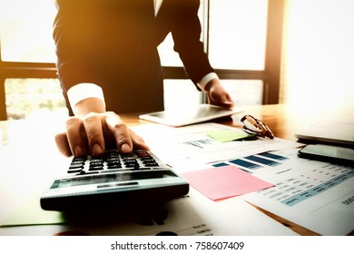 businessman accountant analyze income & budget at workplace. financial advisor calculating tax & business invoice, using counting with calculator, tabnet and smartphone on desk in office.