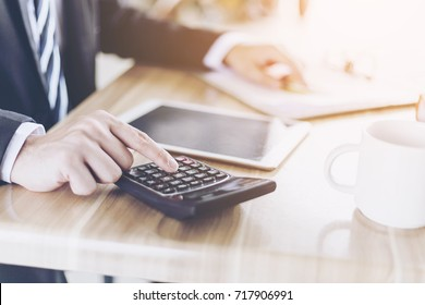 Businessman accountant or banker making calculations. Savings,Business Financing Accounting Banking  and economy Concept. ,Image of hands using calculator on desk about cost at office.