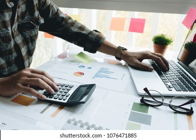 businessman or accountant hand working on calculator to calculate financial data report, accountancy document and laptop computer at office, business concept