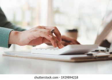 businessman or accountant hand working on calculator to calculate business data, accounting document and laptop computer at office, business concept
