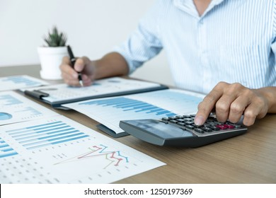Businessman accountant making working audit and calculating expense financial annual financial report balance sheet statement, doing finance making notes on paper checking inspection.