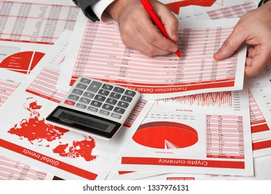 Businessman accountant using calculator for calculating crypto currency report on desk office. Business financial accounting concept Red reports and graphs.