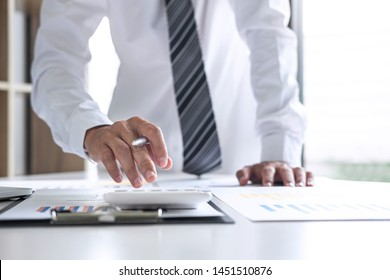 Businessman accountant working analyzing and calculating expense annual financial report balance sheet statement, doing finance making notes on report, Financing Accounting Banking Concept.