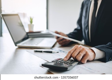 Businessman accountant working new project on laptop computer with report document and analyze document graph and diagram, doing finance making notes statistics.
