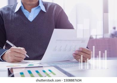 Empresario o contable que trabaja en la oficina revisando periódicamente los estados financieros para la actuación profesional.