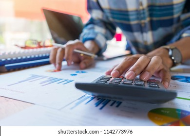 Businessman or accountant working on calculator to calculate financial data report, accounting document and laptop computer. Business financial and accounting concept