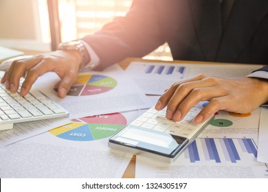 Businessman or accountant working on calculator to calculate business data concept. Accounting,investment advisor consulting situation on the financial report and planning a marketing plan at office.