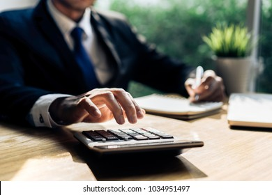 Businessman accouting management with calculator marketing report taking note balance of money statement on paperwork in office room