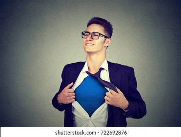 Businessman acting like a super hero tearing his shirt off