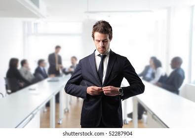 Businessman adjusting his jacket in a meeting room