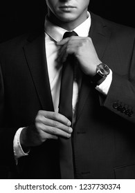 businessman adjusting his tie. black and white portrait of man in suit
