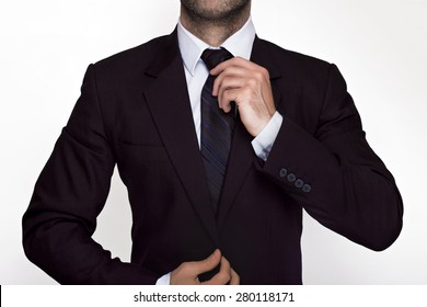 Businessman adjusting his tie and suit
