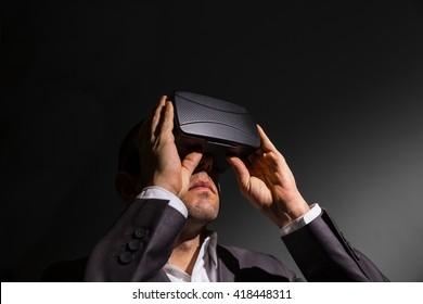 businessman adjusting his virtual reality glasses