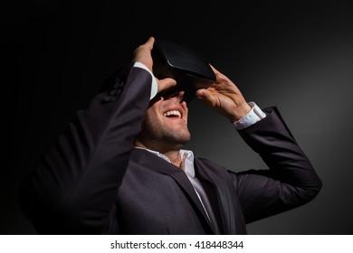 businessman adjusting his virtual reality glasses and smiling