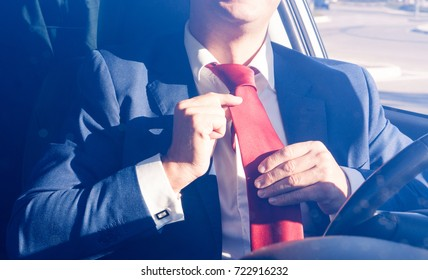 Businessman adjusting necktie inside car at driver seat position - Man wearing elegant dress into automobile ready for business appointment - Morning lights and shadows image main focus on red tie