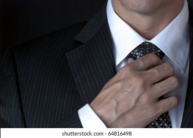 Businessman Adjusting Tie With Right Hand