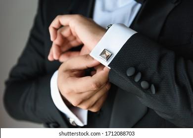 Businessman adjusts his white shirt button .